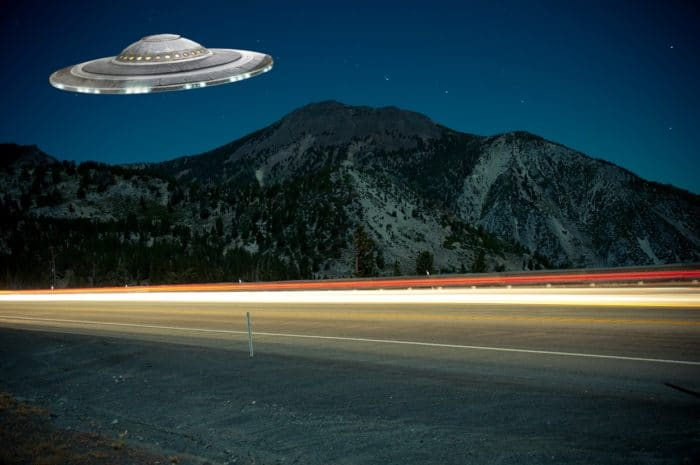 A superimposed UFO over a lonely highway