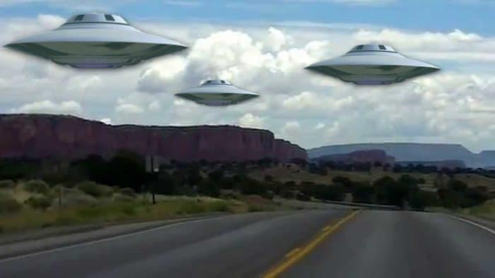 A depiction of UFOs over a New Mexico road