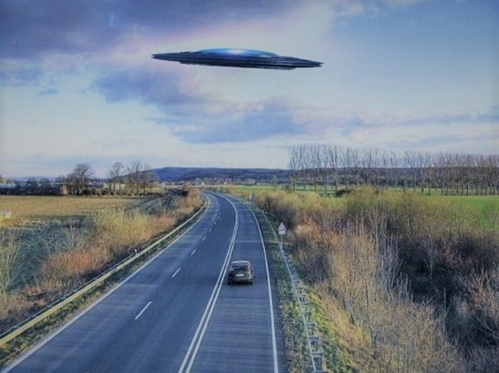 A depiction of a UFO over a road