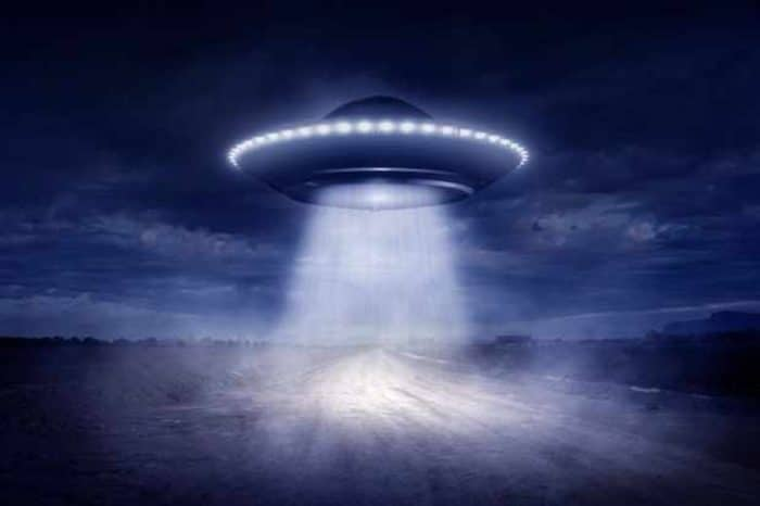 A depiction of a UFO shining a light to the ground
