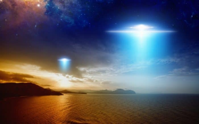 Depiction of two UFOs over the water