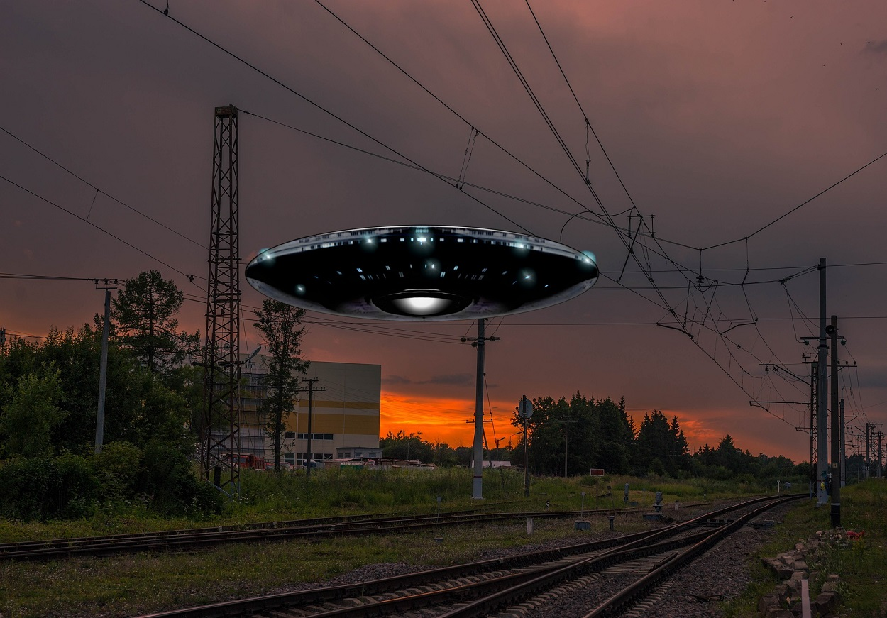 A depiction of a UFO over a rail track
