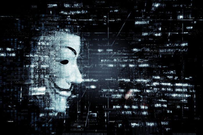 Anonymous mask looking at digital information