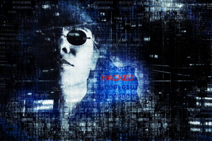 A man in dark glasses behind a computer screen with the word HACKED on it