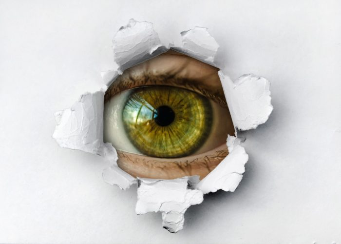 An eye watching through a hole in the wall