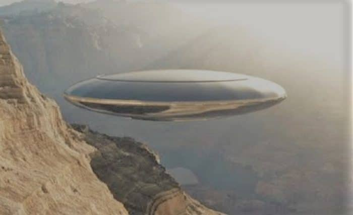 A depiction of a silver UFO over the mountains