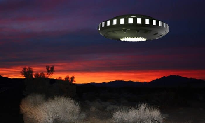 A depiction of a UFO over the mountains