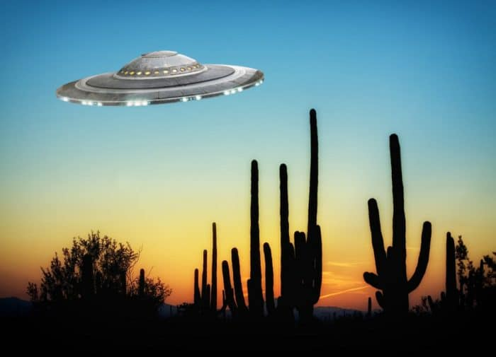 A depiction of a UFO over the desert