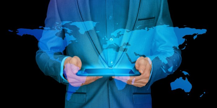 The torso of a suited person holding a tablet with a projection of the world coming from it