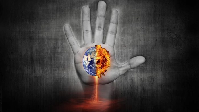 Picture of a single hand with an exploding Earth in the palm