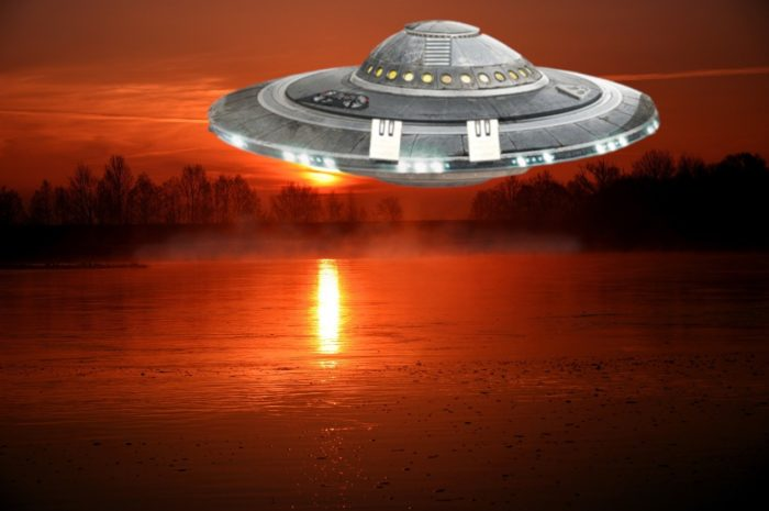 A depiction of a UFO over a river at sunset