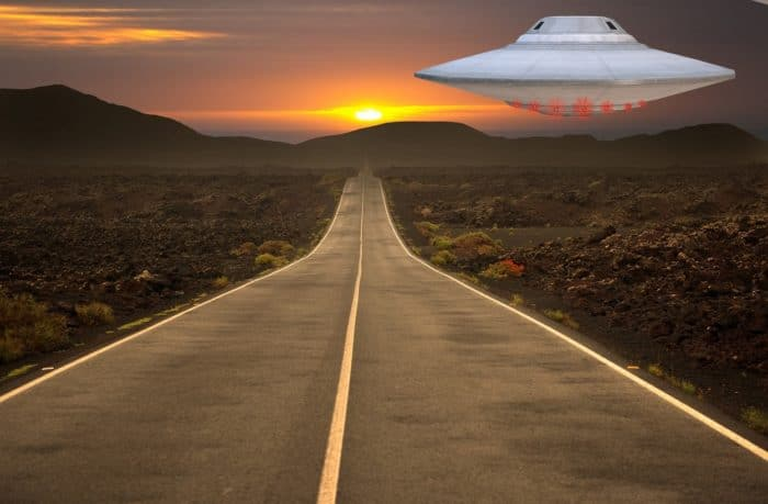 A superimposed UFO over a lonely highway at sunset