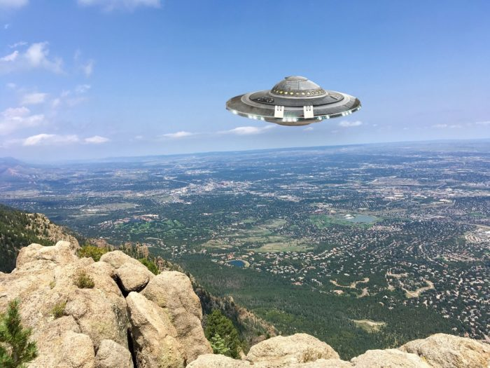 A depiction of a UFO hovering over the mountains