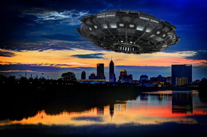 A depiction of a UFO over an Indiana skyline