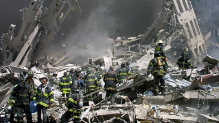 Emergency workers go through the rubble of the collapsed tower