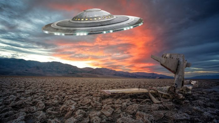 An image of a UFO over a stony ground at sunset