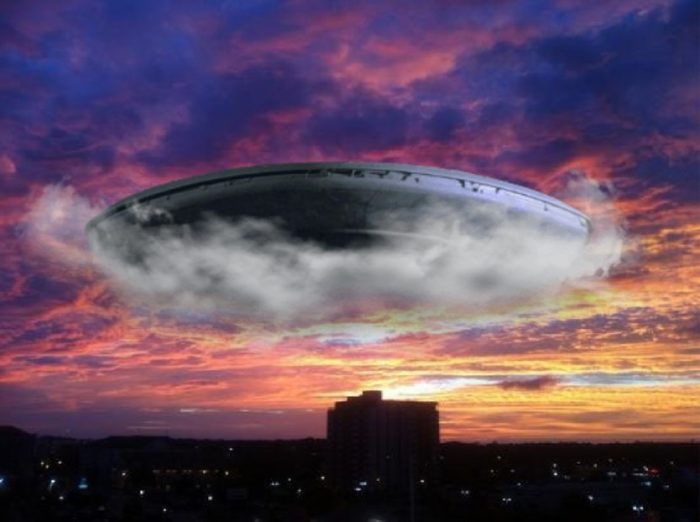 A superimposed UFO over a city at night