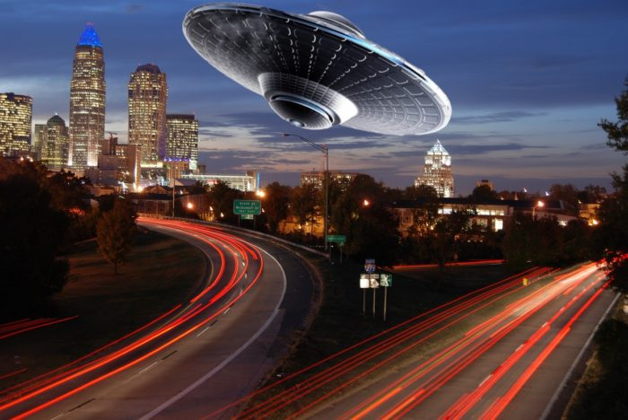 A superimposed UFO over a picture of a time lapsed highway