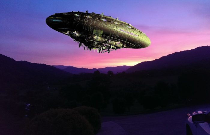 A superimposed UFO on a picture of the mountains at sunset