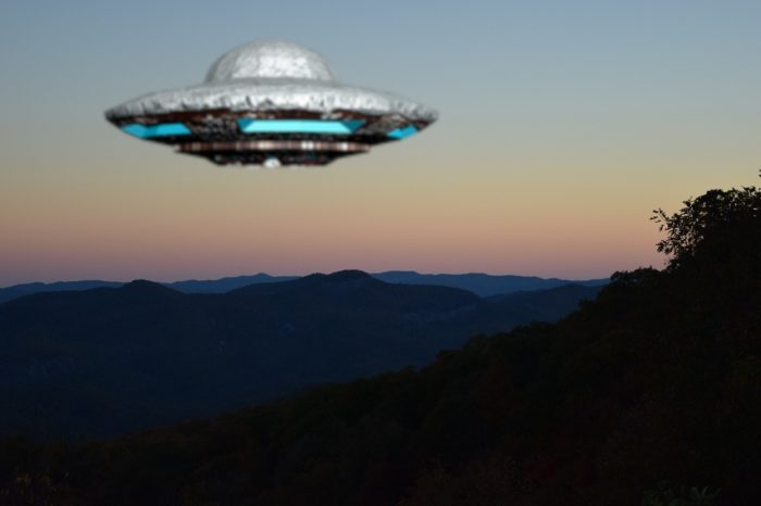 A UFO superimposed over a scene of mountains