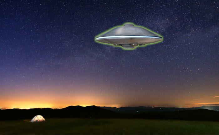A picture of a UFO hovering over a field