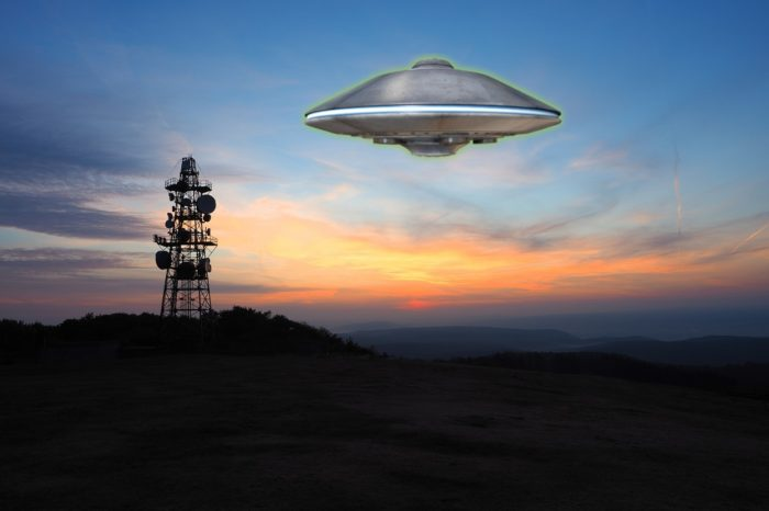 A depiction of a UFO over a radio tower