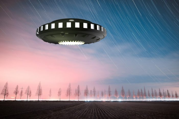 A depiction of a UFO hovering over a field