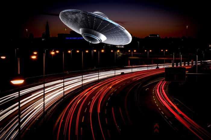 A superimposed UFO over a highway at night