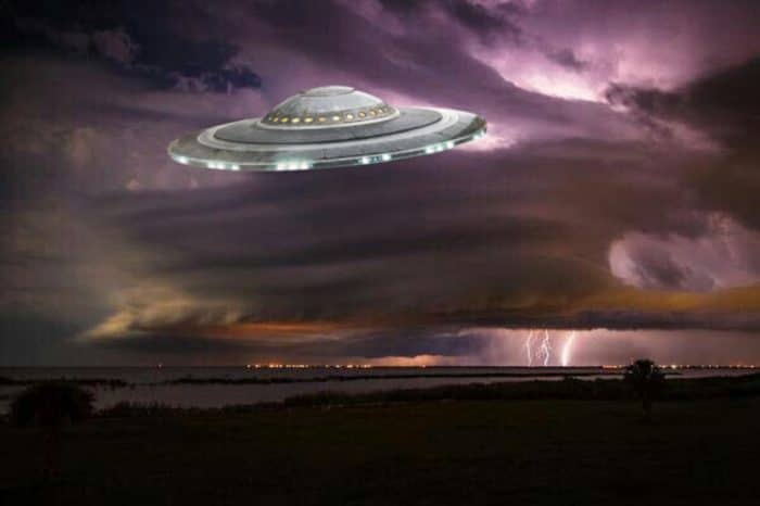A superimposed UFO on a dark cloudy sky