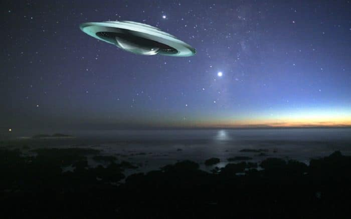 A superimposed UFO over a night coast