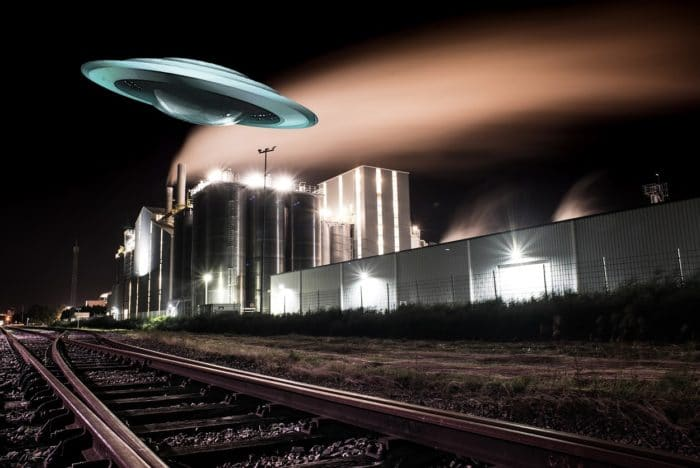 A depiction of a UFO over a power plant