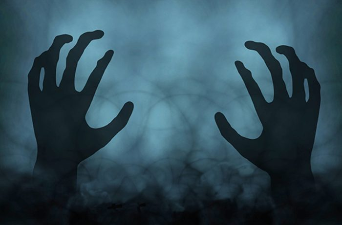A dark misty background with a pair of ghostly hands over the top