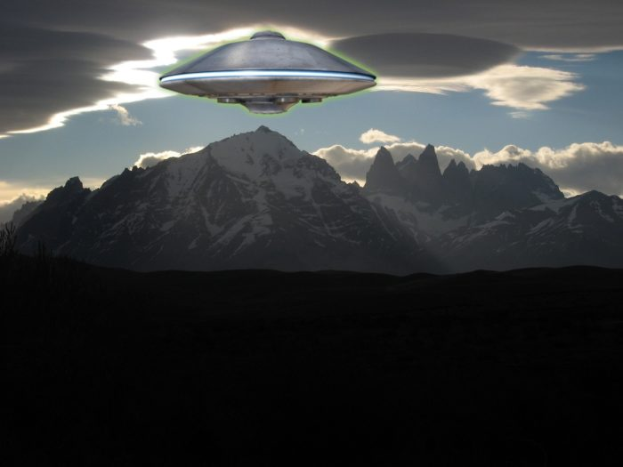 A depiction of a UFO over a mountain