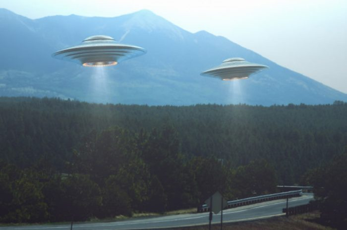 A depiction of UFOs hovering over a highway with surrounding forests