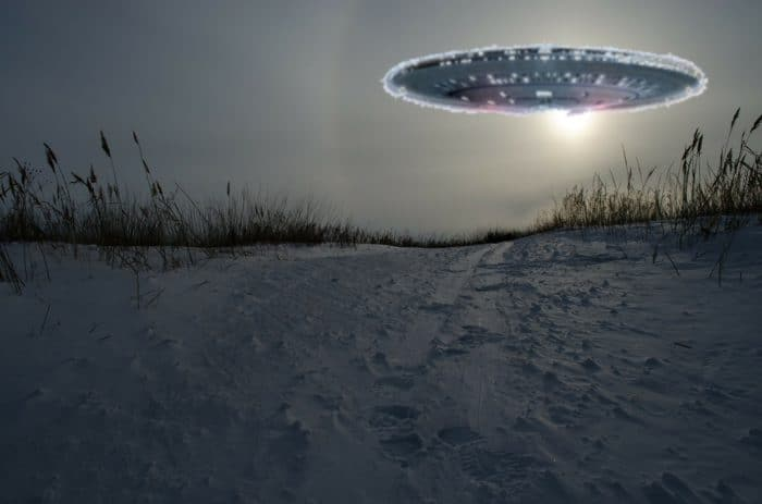 A superimposed UFO over a picture of a snowy hill