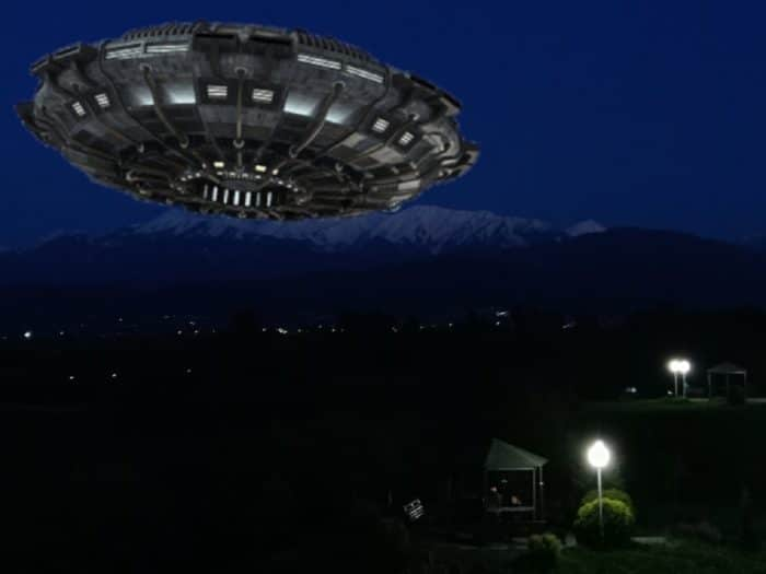 A superimposed UFO over a small mountain village at night