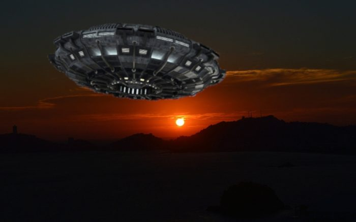 An image of a UFO flying over the mountains at night