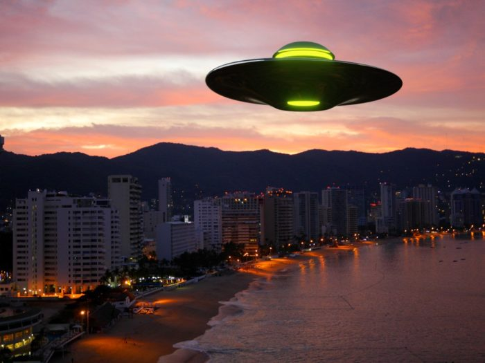 A superimposed UFO over a sunset beach community