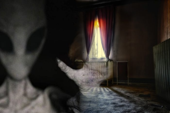 An image of a grey alien over a dark bedroom