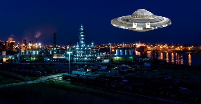 A superimposed UFO over an oil plant at night