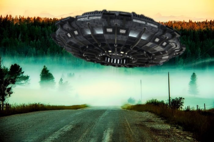 A superimposed UFO over a lonely highway at dawn