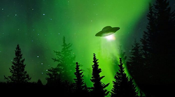 An image of a UFO in a green glowing sky above woodland