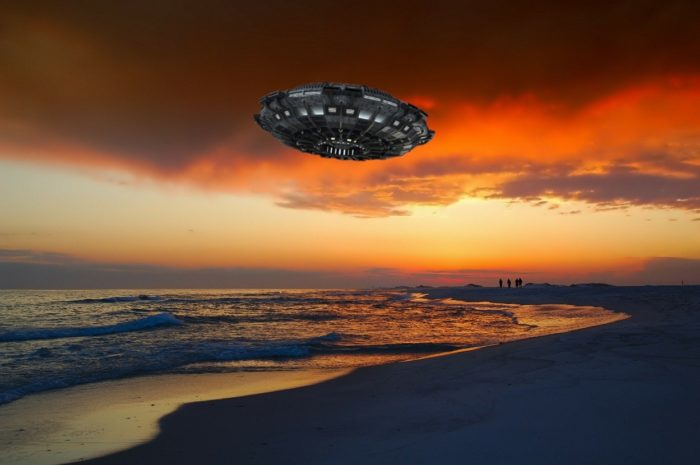 A depiction of a UFO over a beach at sunset