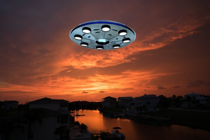 A superimposed UFO on a picture of a riverside community
