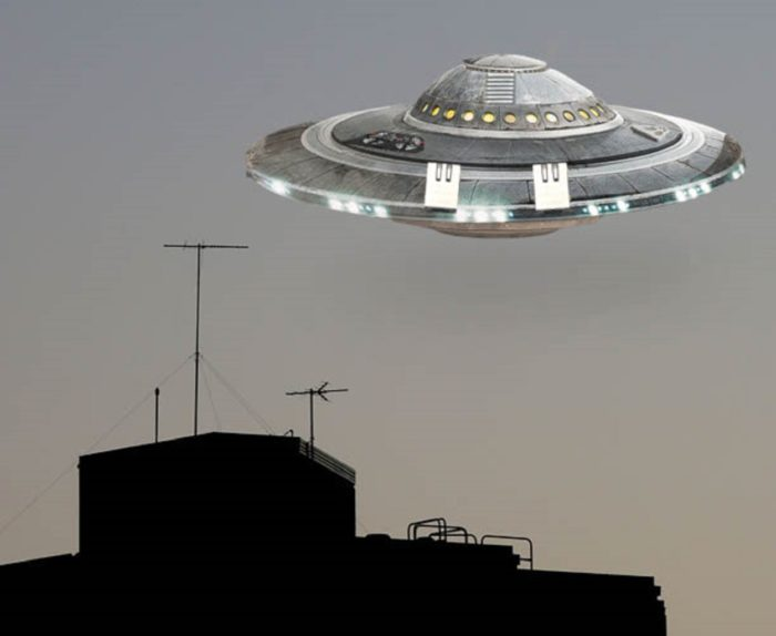 A superimposed UFO hovering over a building top