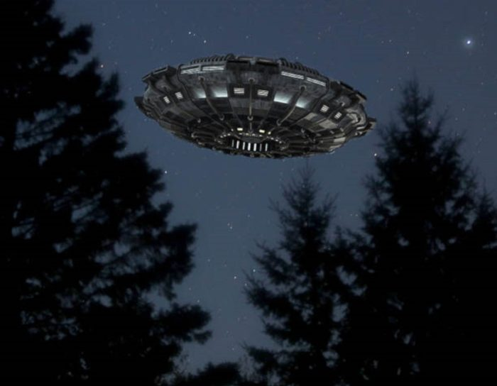 An image of a UFO hovering just above the treetops at night