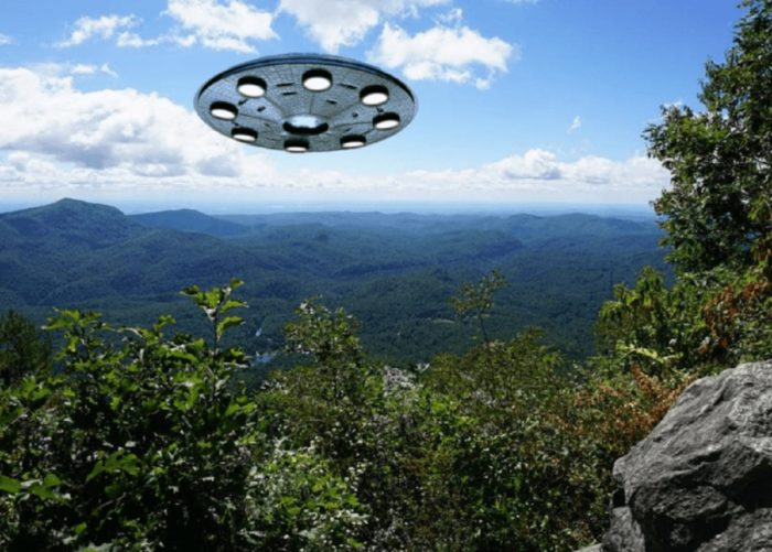 A superimposed UFO over a picture of lush mountains
