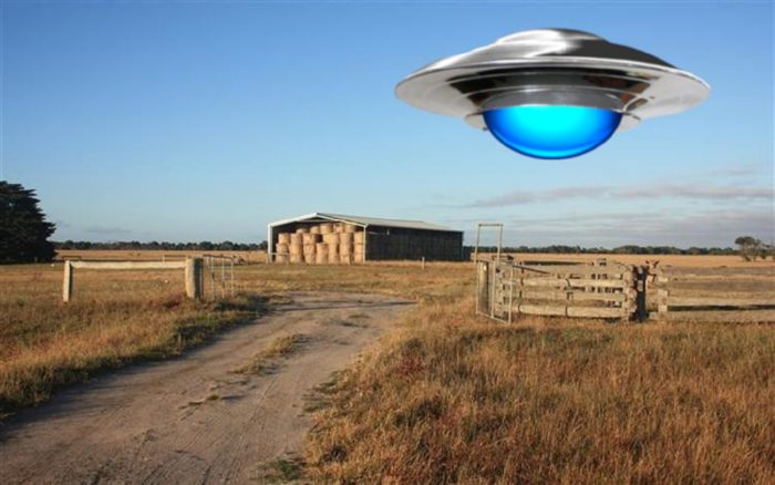 A superimposed UFO over a farm during the day