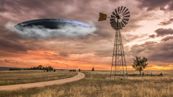 A superimposed UFO emerging from clouds over a picture of a lonely farm