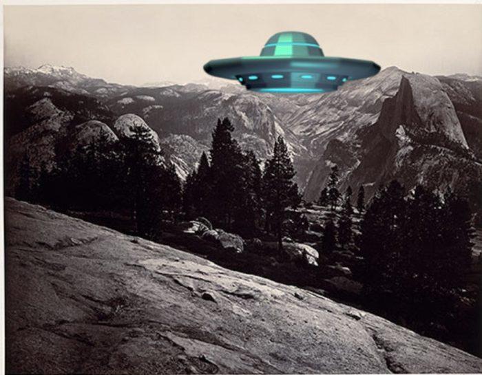 A picture of a UFO superimposed on a picture of mountains and woodlands